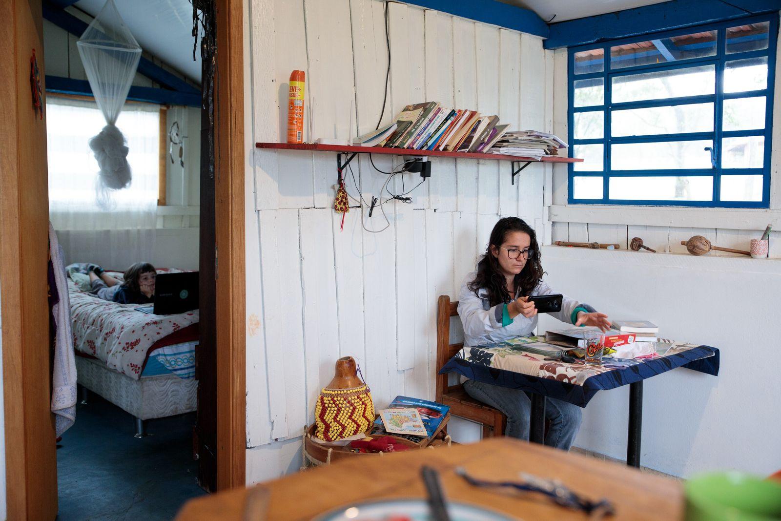 Luisa Brandão, 27, faz reunião com o celular na sala enquanto Aruan, 5, assiste um desenho ...
