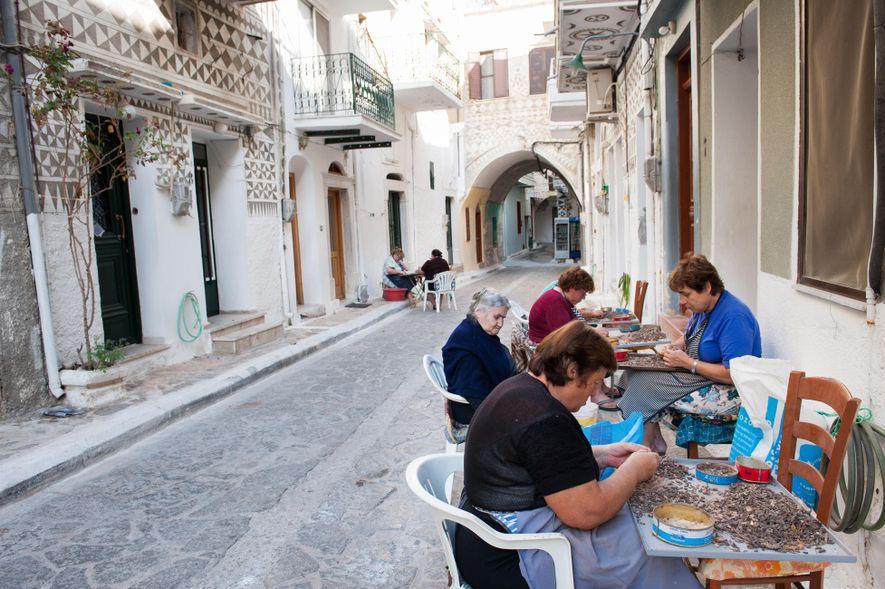 Mulheres extraem gotas de mástique em frente a suas casas em Pyrgi. As construções são decoradas ...