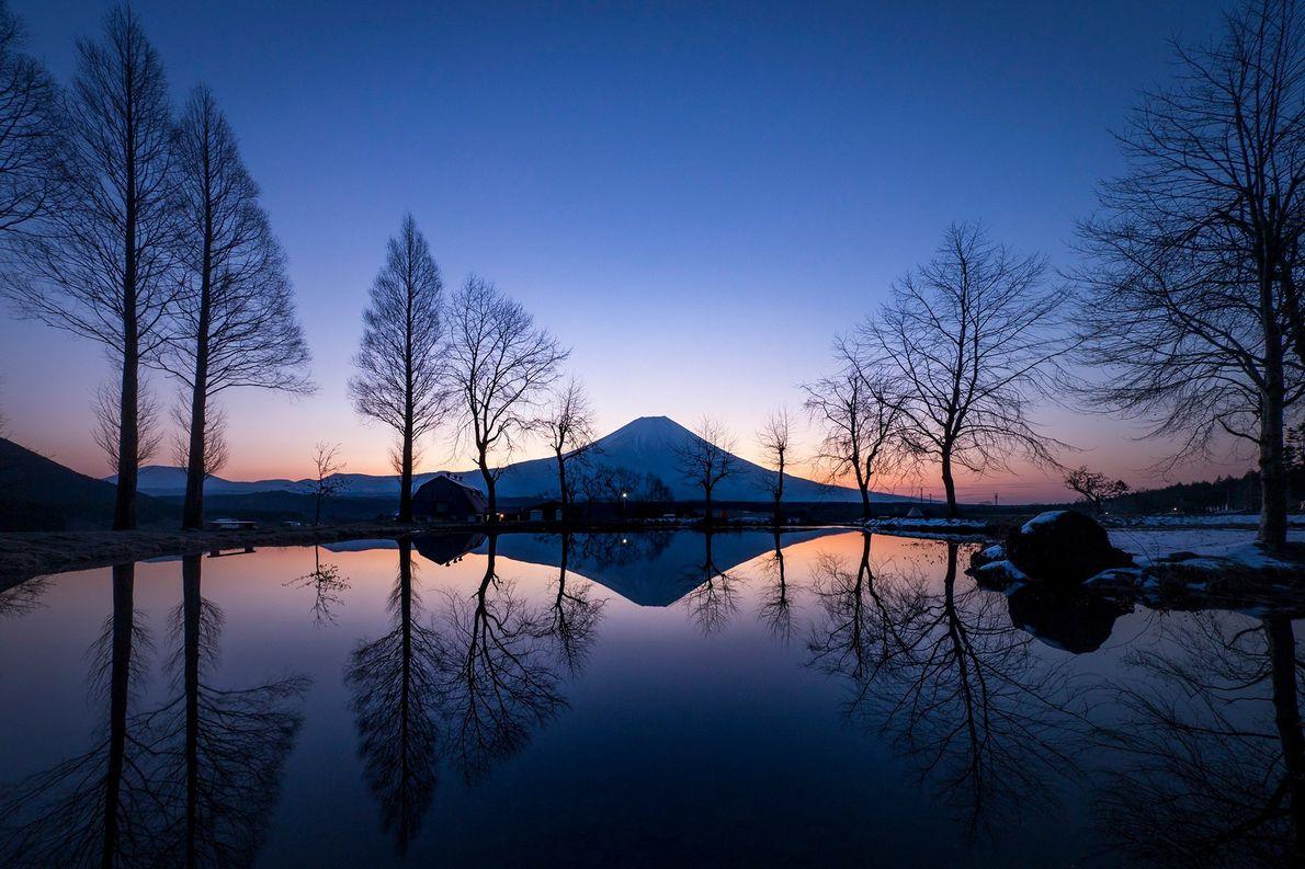 O céu roxo do pôr do sol é refletido no pequeno lago em frente ao Monte ...