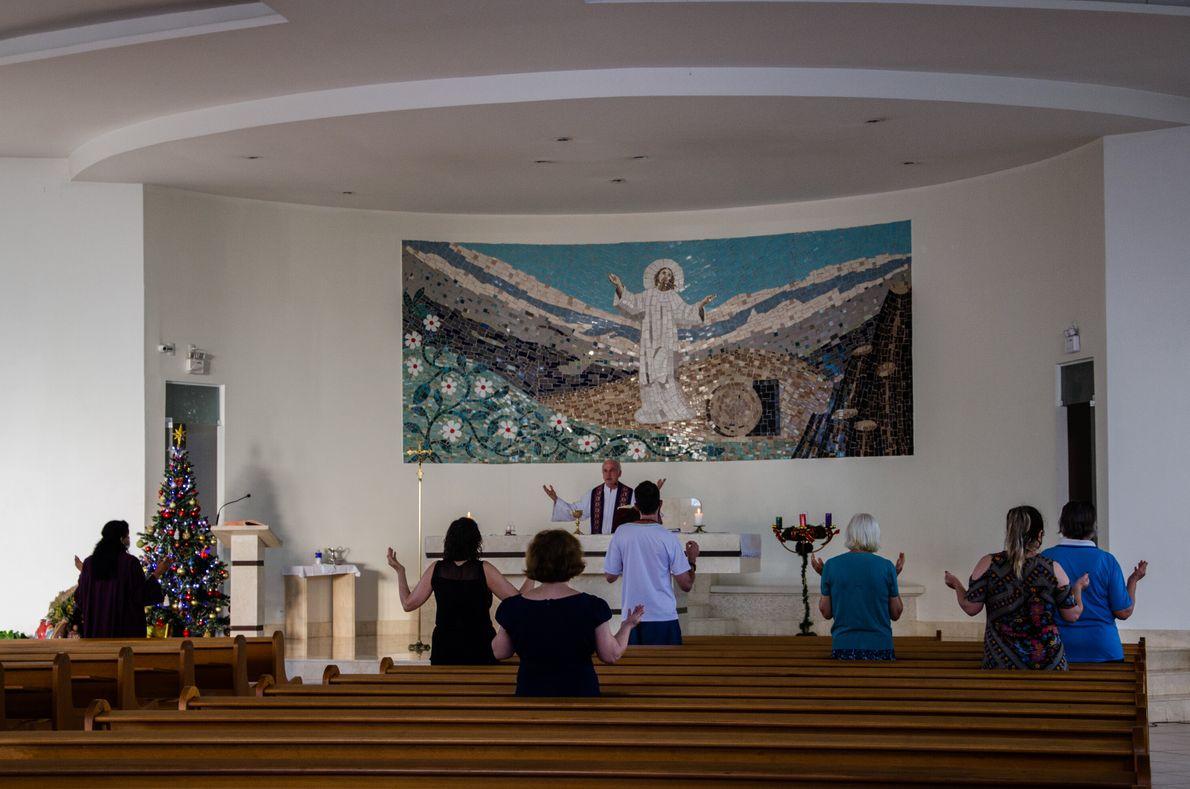Nos períodos de arrefecimento da pandemia, algumas igrejas celebram missas presenciais com medidas de distanciamento social, ...
