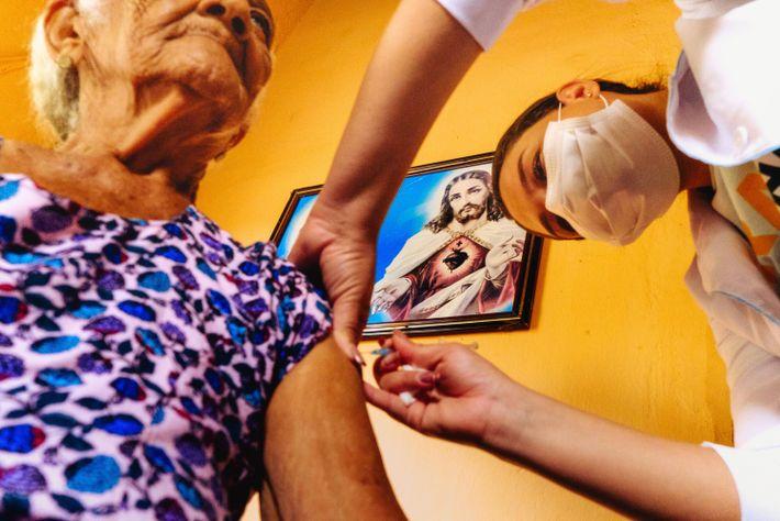 A técnica de enfermagem Raiane Rocha de Melo, 26 anos, à direita, aplica vacina na dona ...