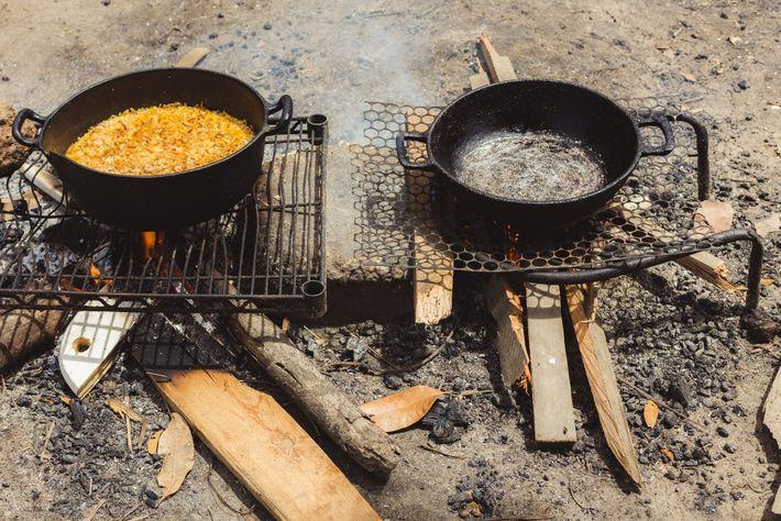Imigrantes cozinham em fogo aberto aceso com restos de madeira no acampamento improvisado próximo à rodoviária ...