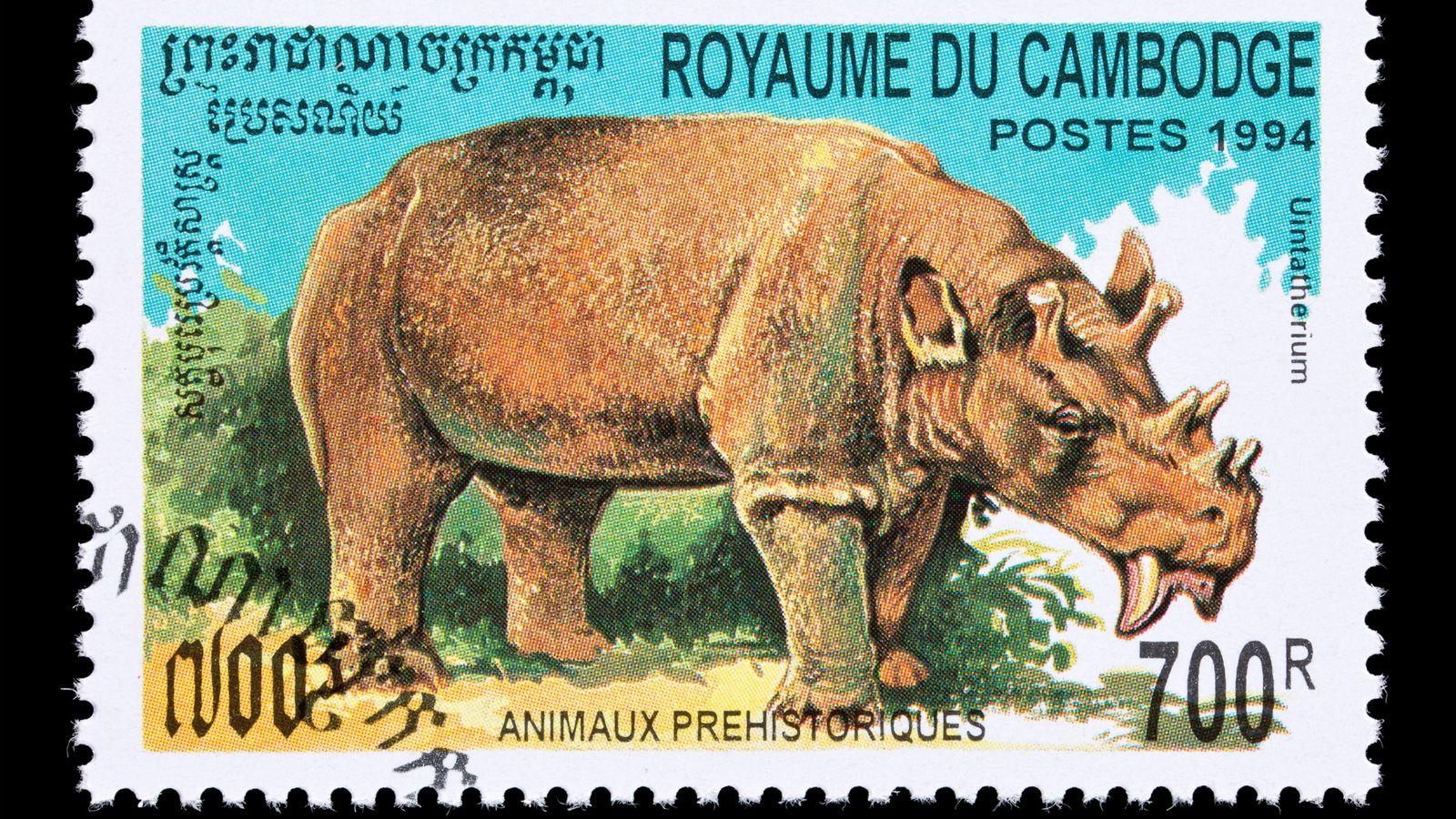 O extinto mamífero uintatério, representado aqui em um selo postal do Camboja, viveu há cerca de ...