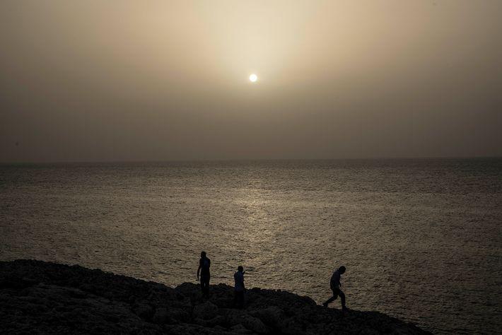 Pessoas assistem ao pôr do sol de cores incomuns, tingido pela nuvem de poeira do Saara ...