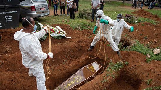 A família de Diva Barbosa observa a uma distância segura enquanto funcionários de uma funerária no ...