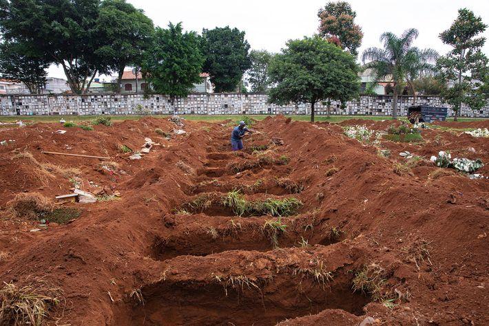 Um coveiro limpa as valas no Cemitério da Vila Formosa. Um dos três cemitérios públicos de ...