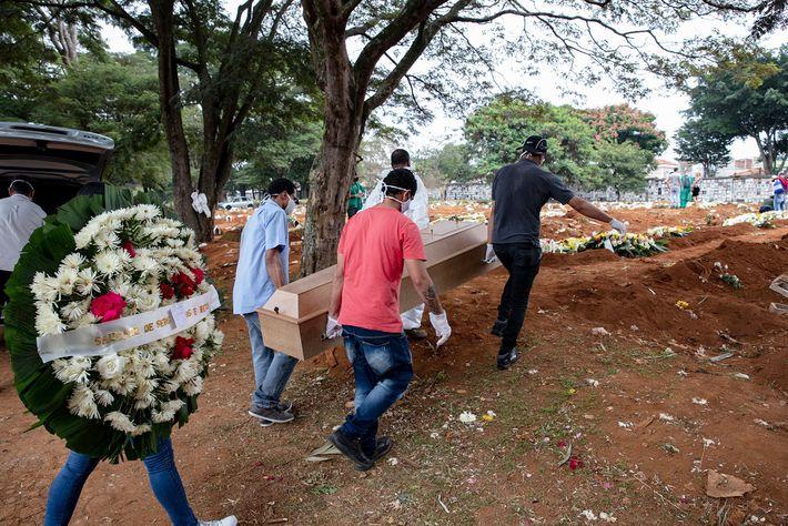 Os filhos de Manoel Joaquim da Silva ajudando a levar o caixão lacrado do pai para ...