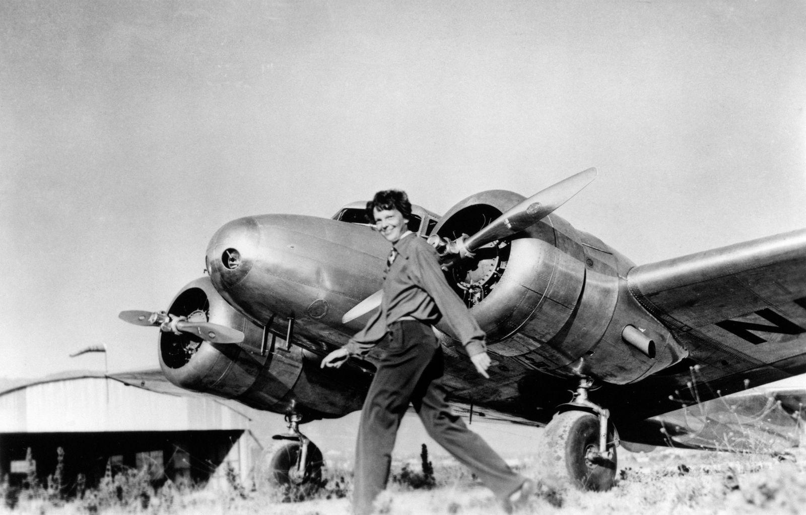 Amelia Earhart caminha em frente ao Lockheed Electra, avião no qual ela desapareceu em julho de ...
