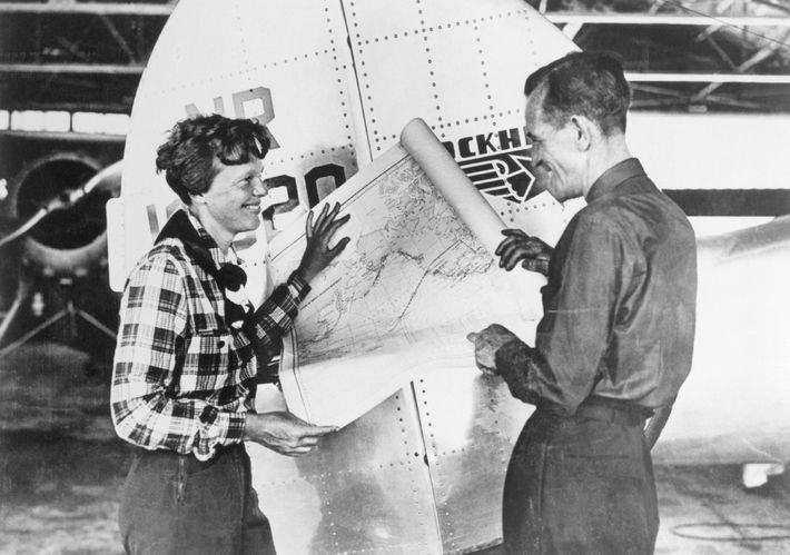 Earhart e o navegador Fred Noonan consultam um mapa do Pacífico que mostra a rota traçada ...