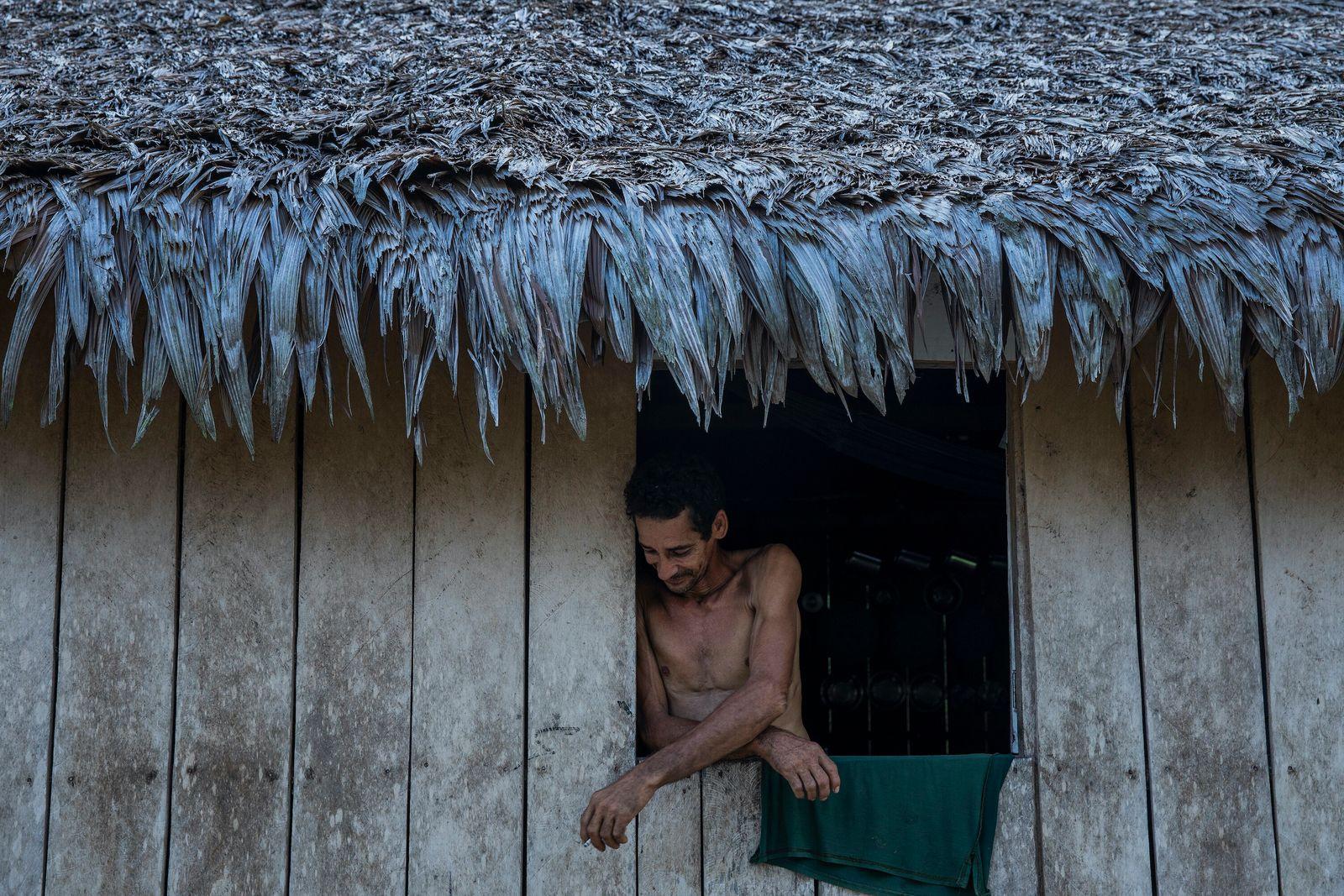 ribeirinho retratado na janela da casa de madeira