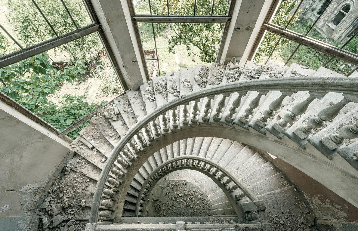 A natureza invade esta escada em espiral, que está se desintegrando.
