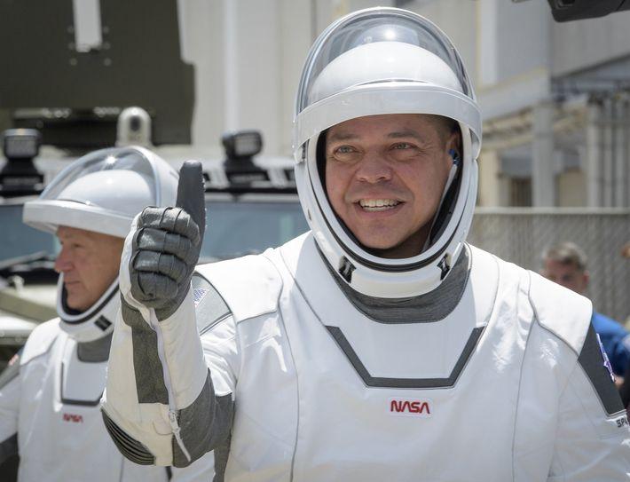 O astronauta Robert Behnken dá um joia enquanto caminha para a plataforma de lançamento com Doug ...