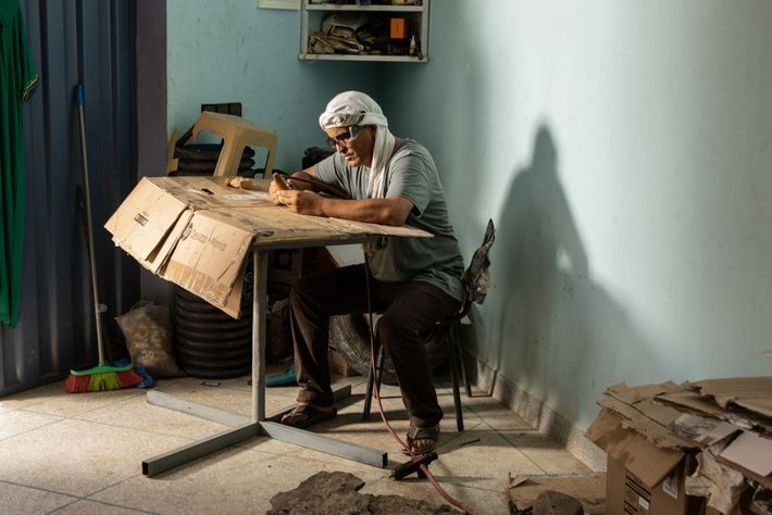 Mohand Ihmadi, dono do Centro Trilobitas Ihmadi, em Alnif, Marrocos, prepara um dente deSpinosauruspara a venda. ...
