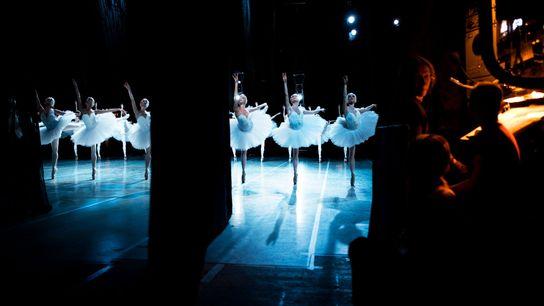 Bailarinas dançam no teatro de balé Mariinski, visto dos bastidores.