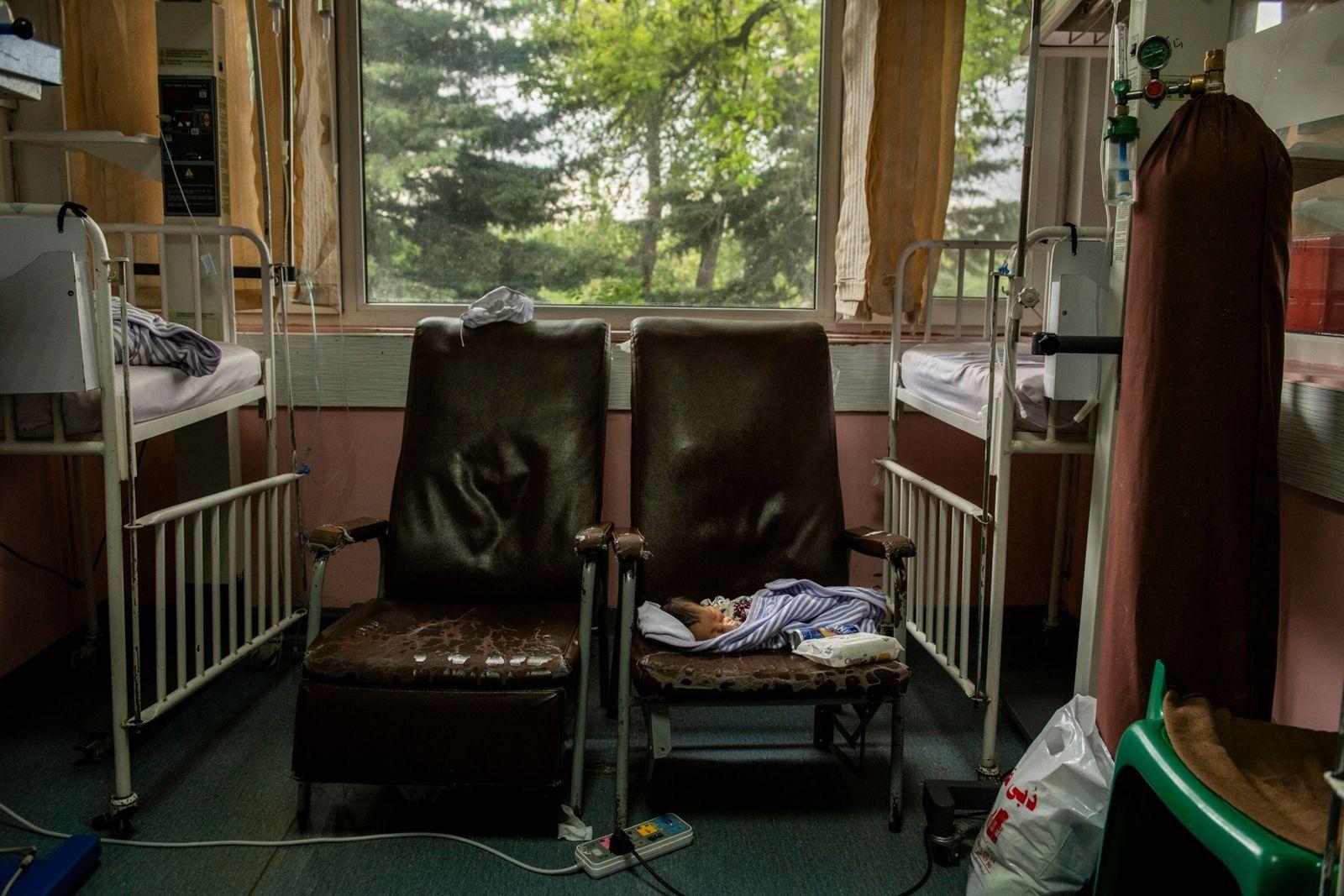 Um bebê de três dias repousa em uma cadeira depois de ser amamentado por sua mãe ...