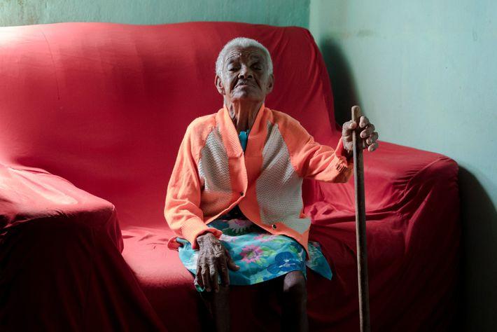 Dona Umbelina posa para o retrato segurando um cabo de vassoura que mais parece um cetro. ...