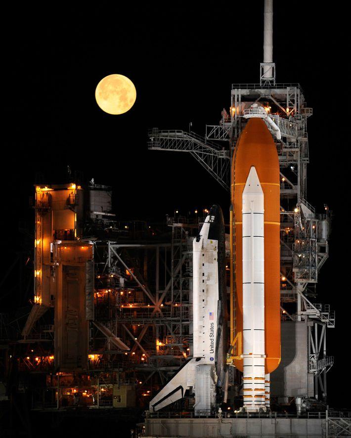 A espaçonave Discovery parada em plataforma de lançamento no Centro Espacial Kennedy, Flórida, com uma lua ...