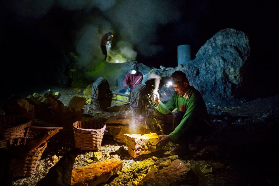 Mineradores quebram blocos de enxofre dentro da cratera do vulcão e enchem cestas de vime para ...