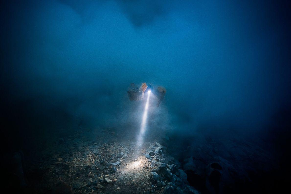 Um farol de minerador corta a escuridão e o gás vulcânico. Os mineradores começam frequentemente o ...