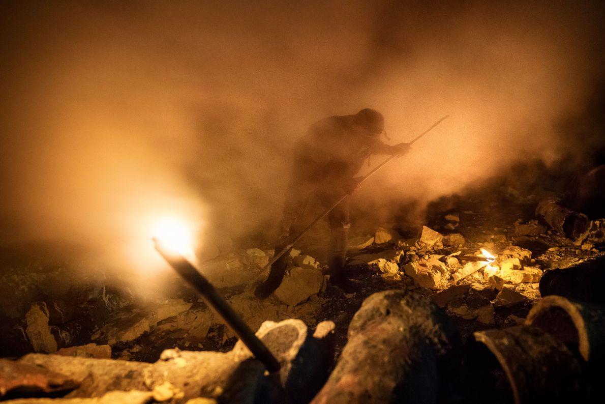 Envolto em gás sulfúrico, um minerador usa um mastro de metal para extrair pedaços de enxofre.