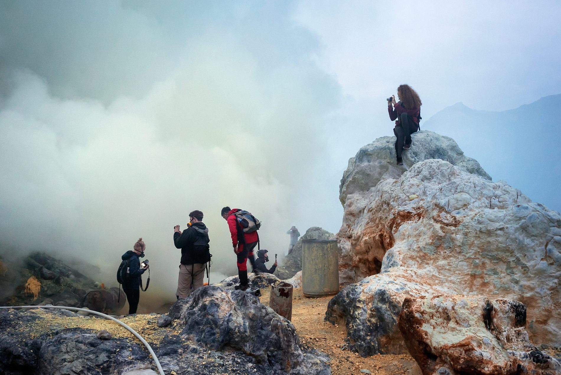 Turistas equipados com máscaras de gás tiram fotos da costa da cratera onde o Lago Cratera ...