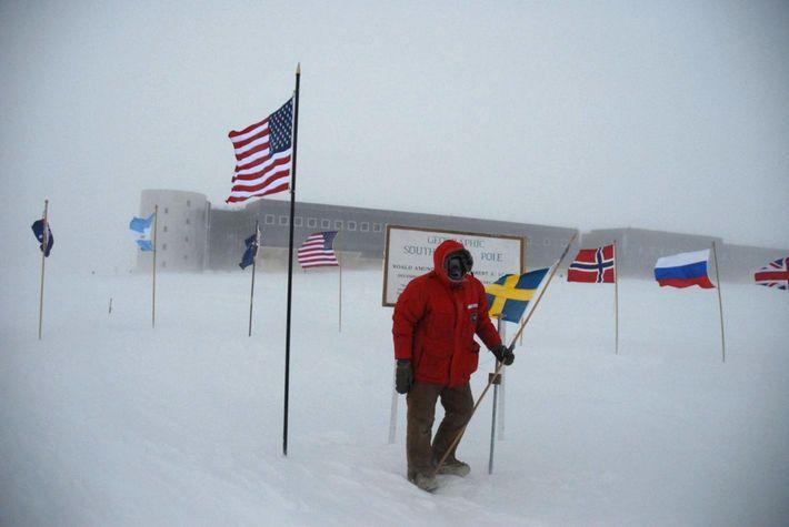 Sven Lidström no Polo Sul, com a estação Amundsen-Scott ao fundo.