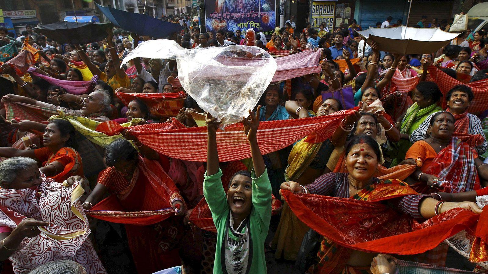 Um menino segura uma sacola plástica para receber arroz distribuído como oferenda pela autoridade do templo ...
