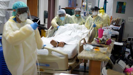 Profissionais de saúde transferem um paciente na Unidade de Tratamento da Covid-19 no United Memorial Medical ...