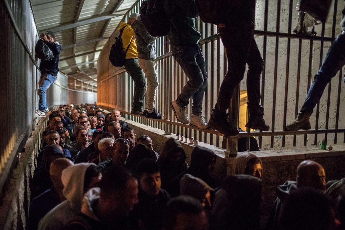 No posto de controle 300, próximo a Belém, Palestinos da Cisjordânia, alguns escalando as grades para ...