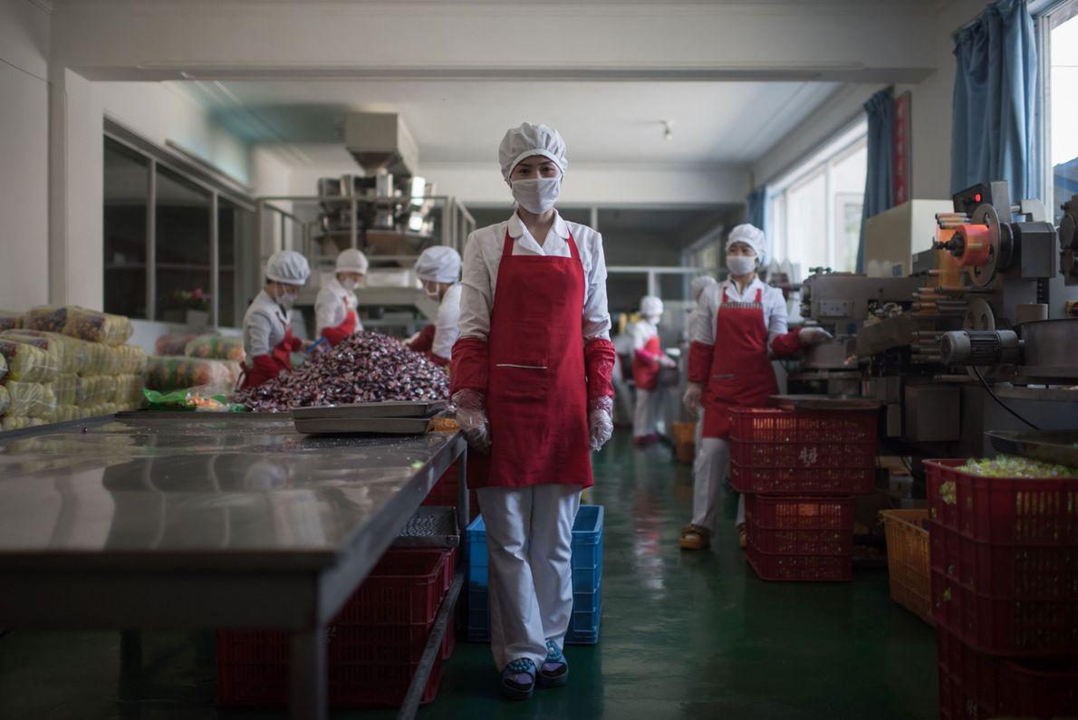Hong Kum Ju, 27, em frente à fabrica de comida onde trabalha, perto da cidade portuária ...