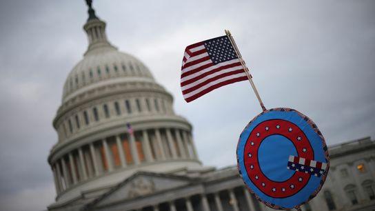 Apoiadores do presidente dos Estados Unidos, Donald Trump, erguem bandeira dos Estados Unidos sobre um símbolo ...