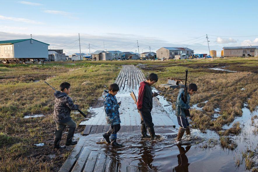 O vilarejo de Newtok, com 380 habitantes, está afundando à medida que o permafrost abaixo dele descongela. Em uma caçada de verão, quatro meninos yupik — da esquerda para direita, Kenyon Kassaiuli, Jonah Andy, Larry Charles e Reese John — atravessam uma passagem inundada.