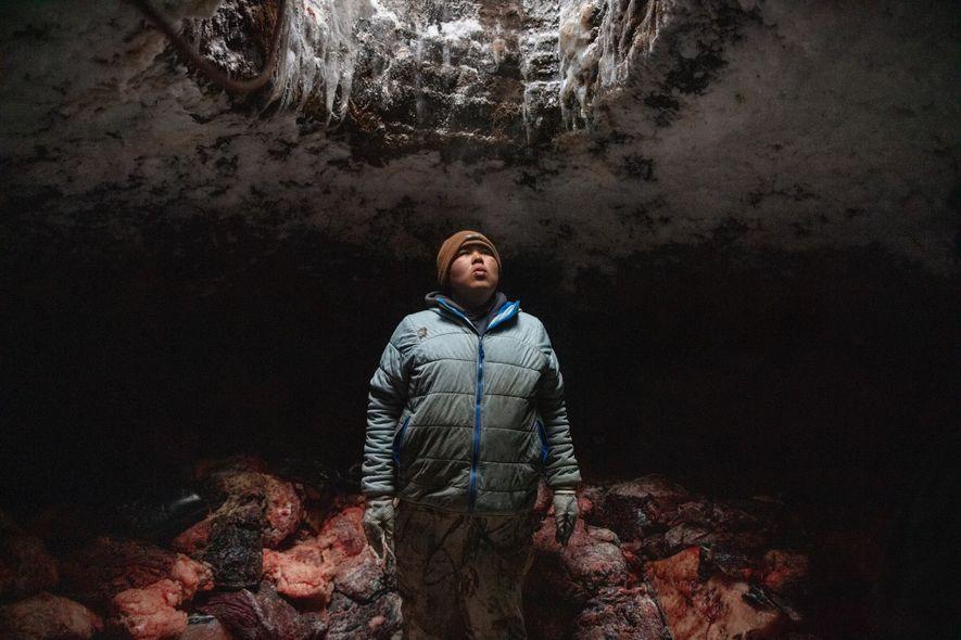 Josiah Olemaun, um jovem baleeiro inupiat em Utqiaġvik (Barrow), no Alasca, descansa após empilhar carne de baleia no porão de permafrost de sua família.