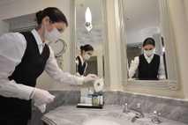 Uma funcionária coloca máscaras faciais no banheiro de uma suíte do famoso Hotel Adlon Kempinski de ...