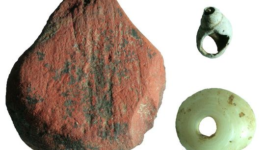 O objeto de coloração ocre-vermelho junto com contas ornamentais feitas de conchas foi descoberto no sítio ...