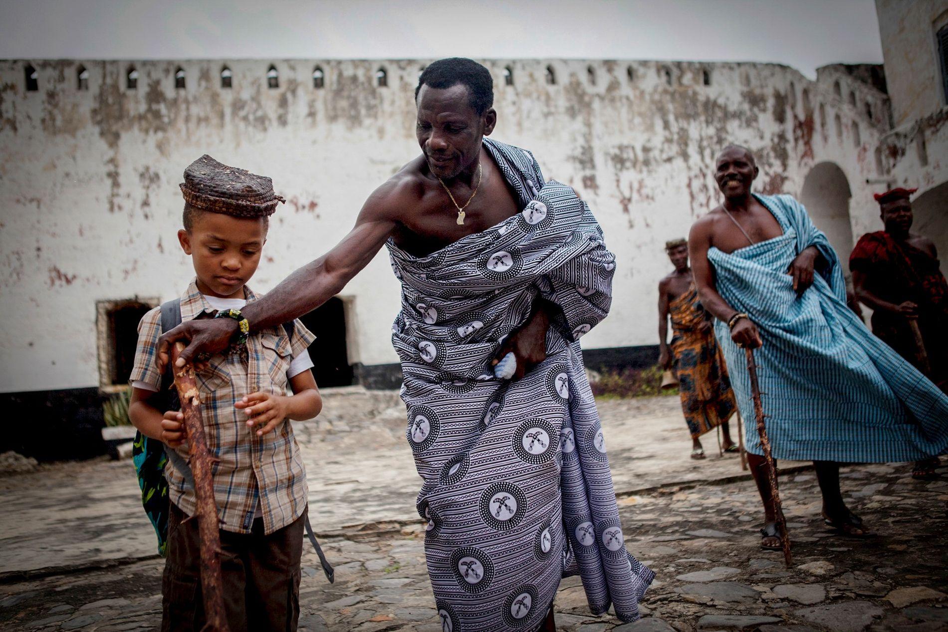 Em Anomabo, Gana, um homem faz ajustes no cajado de um jovem turista em Fort William, ...