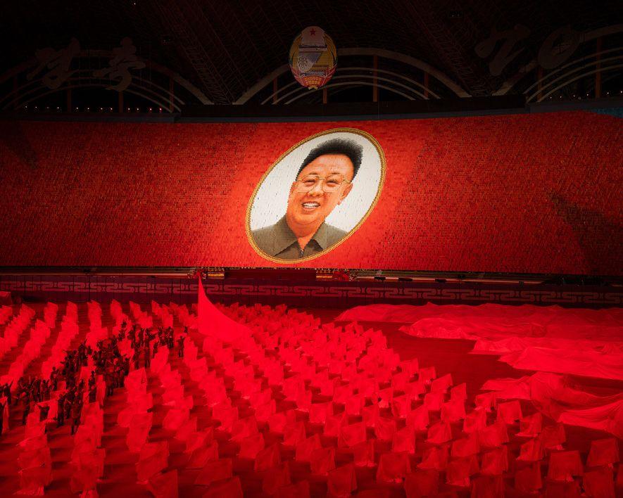 Um retrato imenso de Kim Jong-il, o segundo Líder Supremo da Coreia do Norte, acima dos Jogos das Massas, comemoração do 70º aniversário do país.