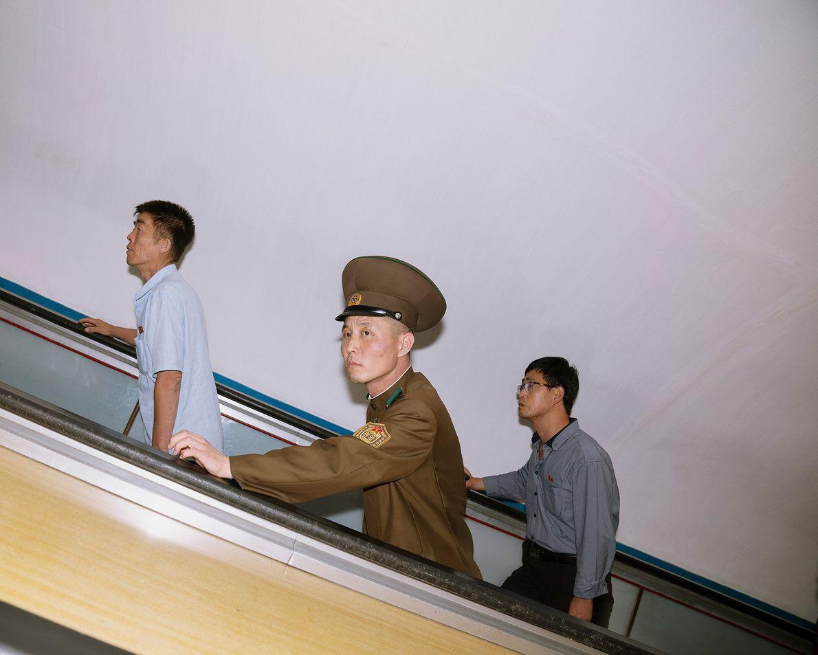 Pessoas indo ao trabalho em uma escada rolante do metrô de Pyongyang.
