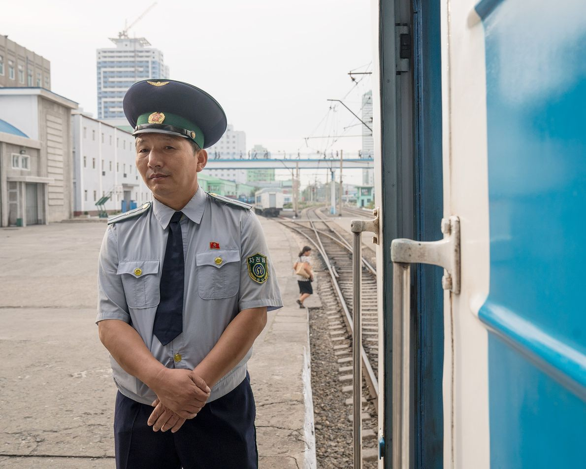 Um trabalhador ferroviário em pé na plataforma da estação de trem de Pyongyang.