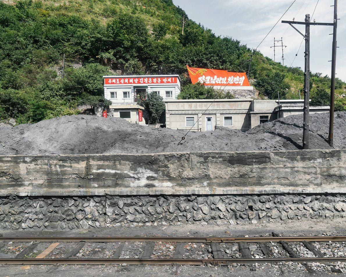 Montes de materiais de construção estendem-se pelos trilhos a caminho de Rason.