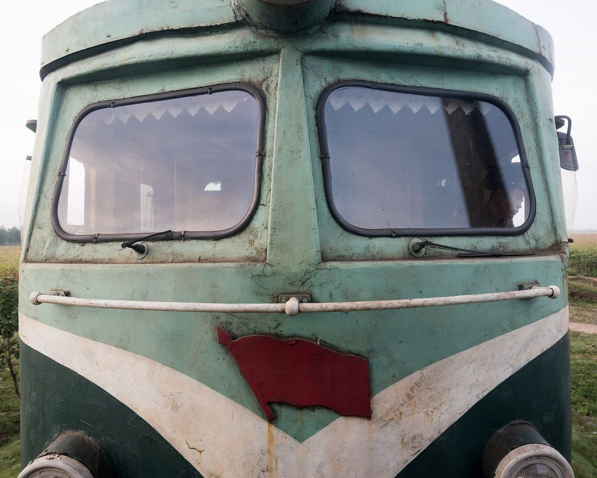 Um trabalhador ferroviário contempla a paisagem que passa pela janela do trem.