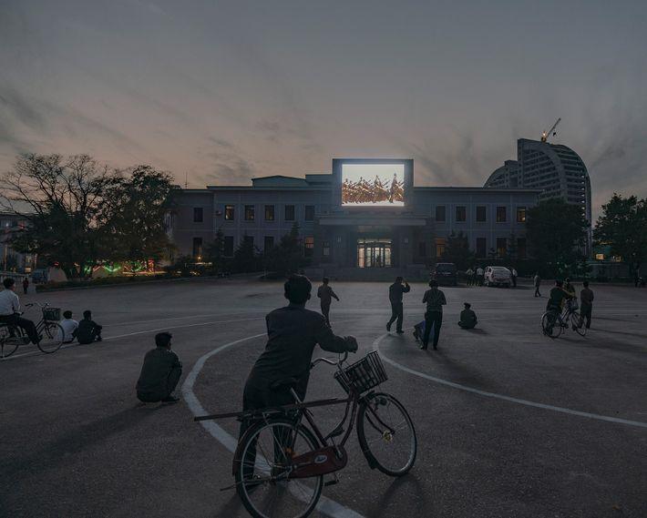 Um vídeo ilumina a praça central de Rason no pôr do sol.