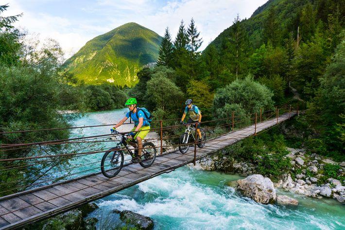 Ciclistas cruzam ponte no Vale do Soča, na Eslovênia.