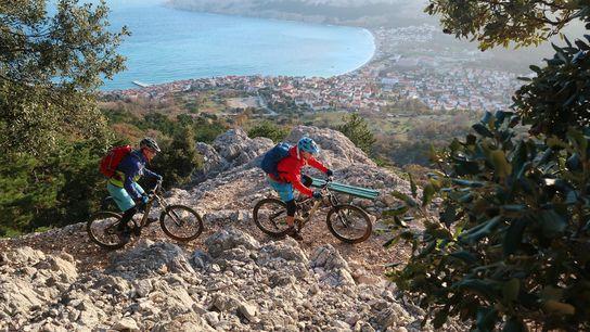 Na Trans Dinarica, ciclistas apreciam a vista da ilha de Krk, na Croácia.