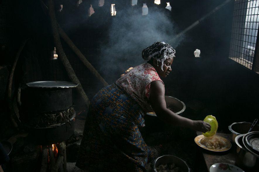 Mama Baker prepara a perca-do-nilo em seu restaurante. A comida dela é um pouco mais cara que a de muitas banquinhas do mercado, mas ela fez negócios o bastante para mandar os filhos para a faculdade em Kampala.
