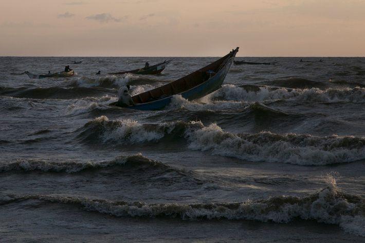 Barcos cortam as águas turbulentas do lago Vitória após uma noite de pescaria. Muitos pescadores lá ...