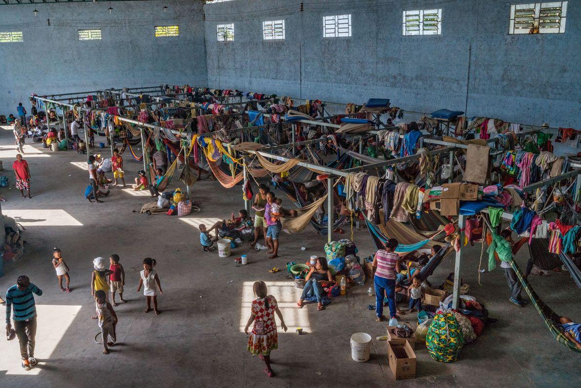Cerca de 500 membros da tribo Warao vivem em um abrigo de concreto equipado com redes ...