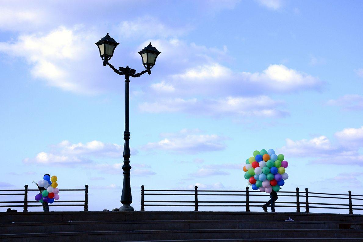 Dois cachos de balões, elegantemente equilibrados em cada lado da moldura, adicionam cores à cena pouco ...