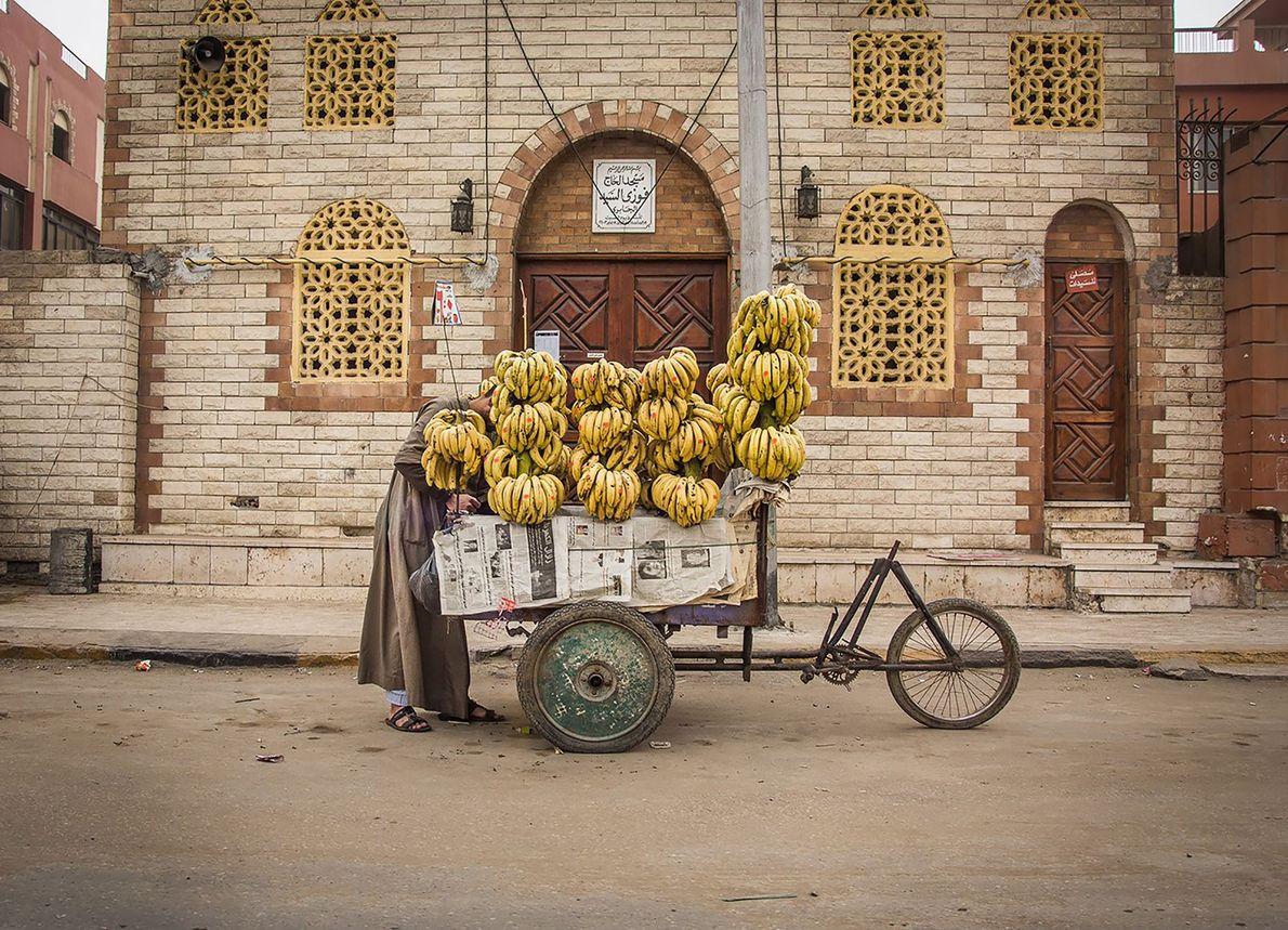 CAIRO Nesta imagem colorida, o vendedor de rua parece desaparecer no grande amontoado de bananas, cujas cores ...